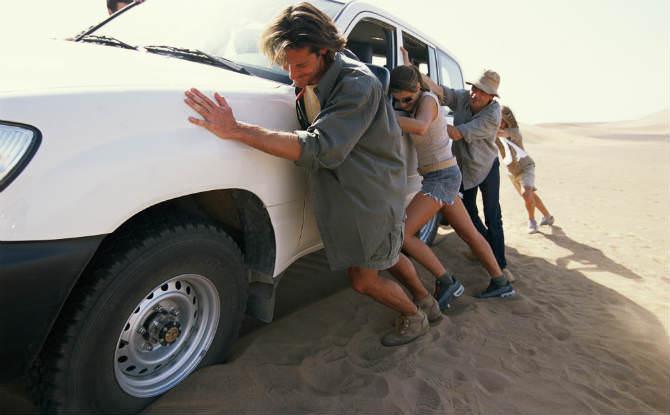 אנשים דוחפים רכב שטח בחול