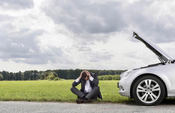 גבר יושבעל הכביש ליד רכב