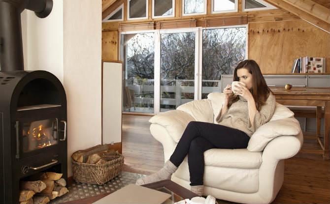 אישה שותה על כורסא מול אח בוער