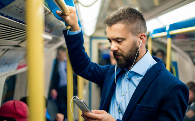 איש עם אוזניות עומד באוטובוס