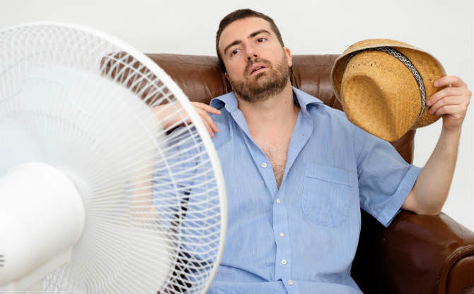 איש סובל מחום מול מאוורר