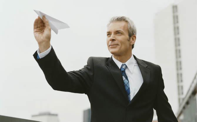 איש עסקים מחזיק מטוס מנייר