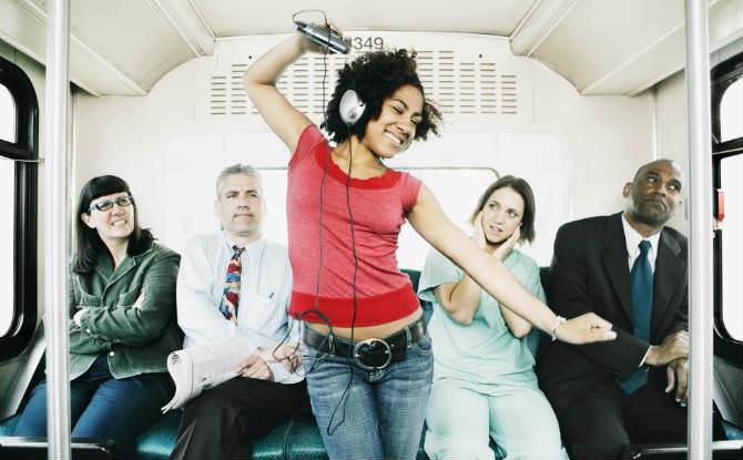 צעירה עם אוזניות רוקדת באוטובוס