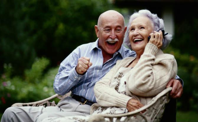 זוג זקנים מחייכים, האישה מדברת בנייד