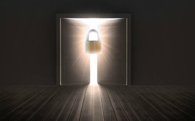 חדר חשוך עם דלת מעט פתוחה שעליה מנעול