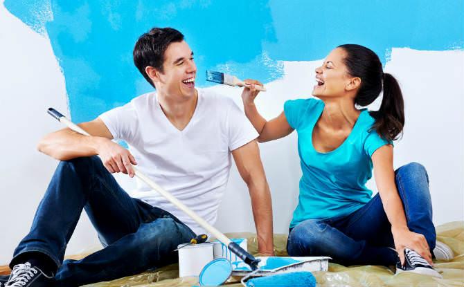 זוג עם מברשות וצבע על רקע קיר צבוע חלקית