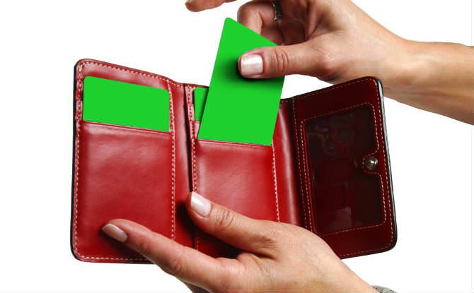 יד מוציאה כרטיס ביקור ירוק מארנק אדום