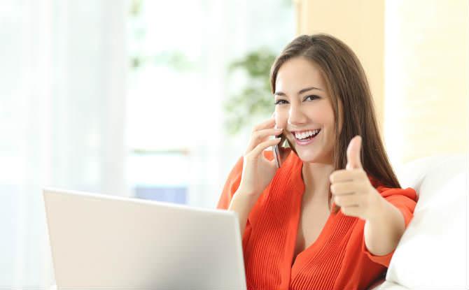 אישה מרוצה בטלפון מול מחשב