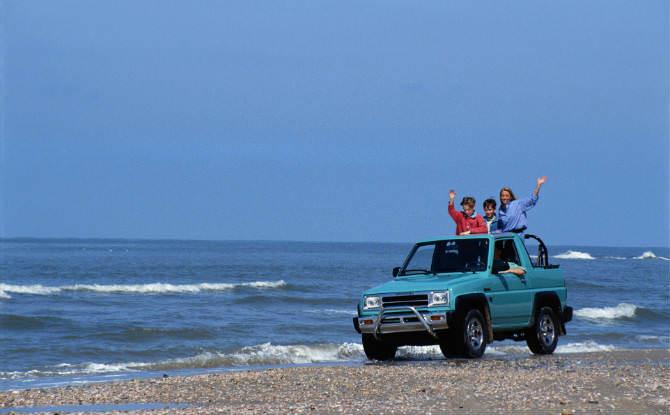 משפחה בג'יפ על חוף הים