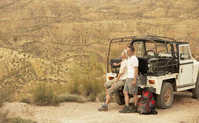 זוג נשען על ג'יפ במדבר