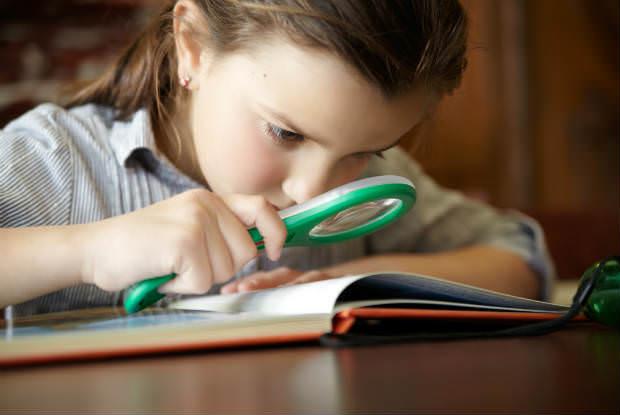 ילדים מתבוננת בספר עם זכוכית מגדלת