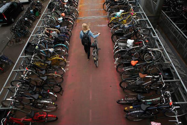 בחורה הולכת בין הרבה אופניים