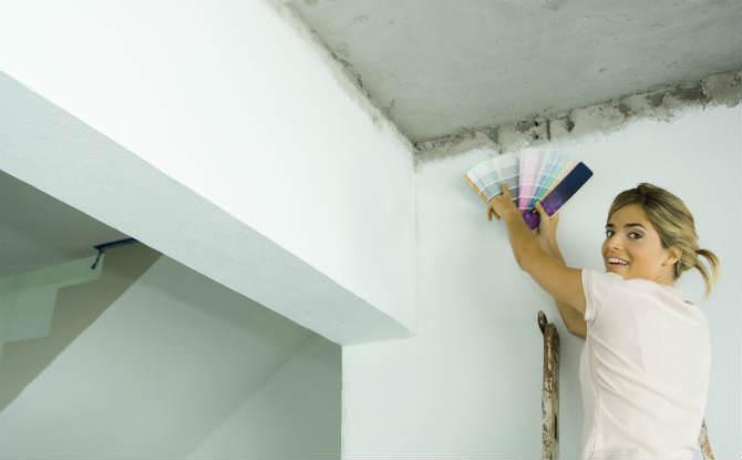 אישה על סולם מתאימה צבעים בשיפוץ