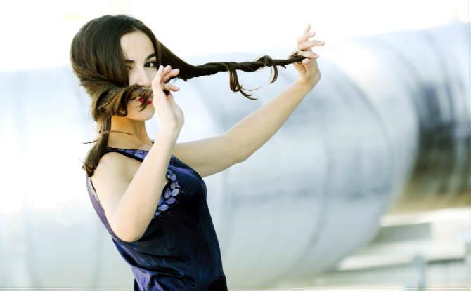 אישה מגלגלת את קצוות שיערה בידיה
