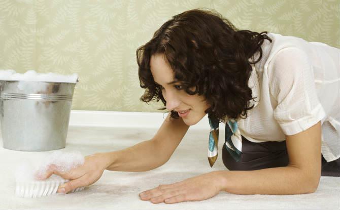 אישה מנקה שטיח עם סבון