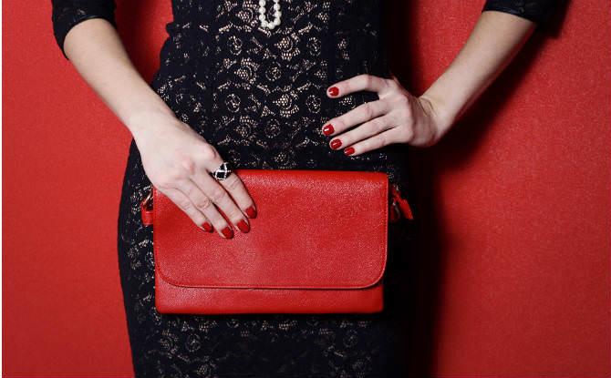 אישה עם שמלה שחורה ותיק אדום