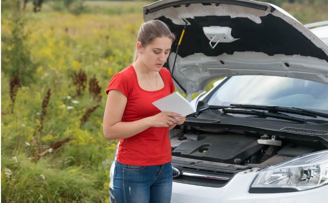 אישה עם רכב תקוע מסתכלת בספר רכב