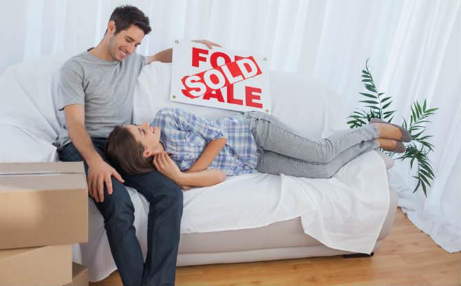 זוג על ספה עם שלט למכירה שעליו כתוב נמכר באנגלית
