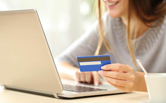 אישה מול לפטופ עם כרטיס אשראי ביד