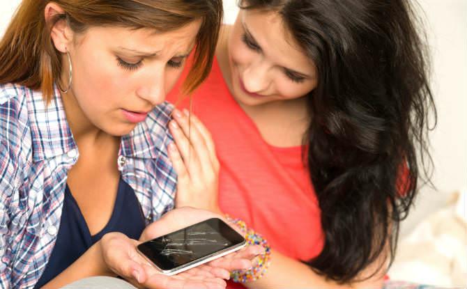 חברה מנחמת אישה עם טלפון שבור ביד