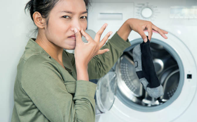 אישה מחזיקה גרב מסריחה שיצאה ממייבש כביסה