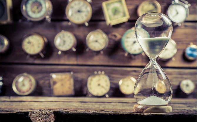 שעון חול והרבה שעוני קיר תלויים מאחור