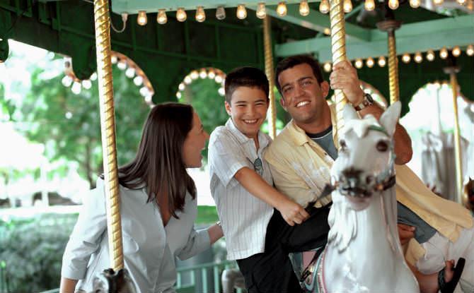 הורים עם ילד על קרוסלה מסתובבת בלונה פארק