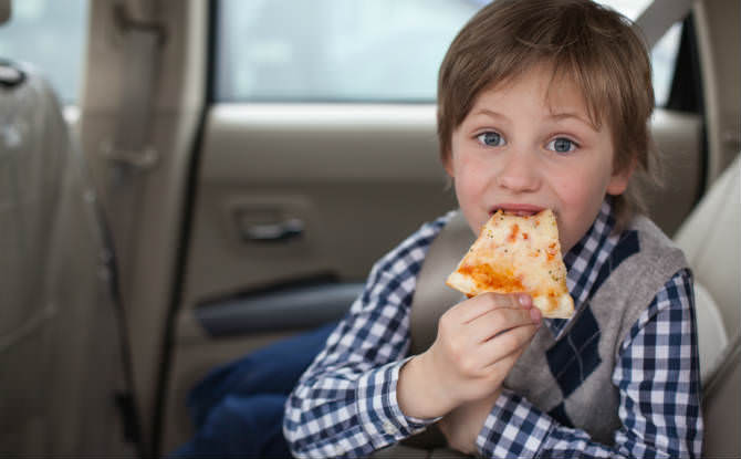 ילד אוכל פיצה באוטו