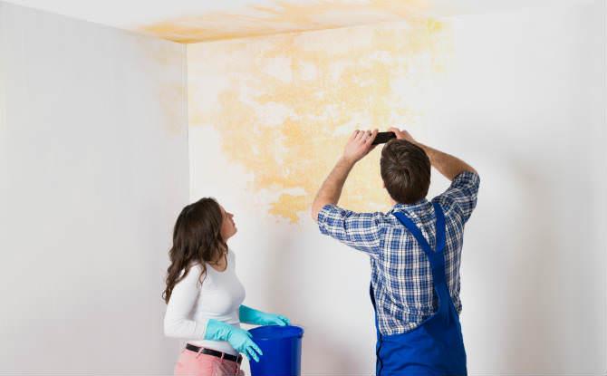 איש ואישה צופים בנזקי רטיבות בקיר