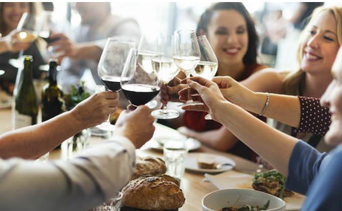 אנשים מרימים כוסות יין במסעדה