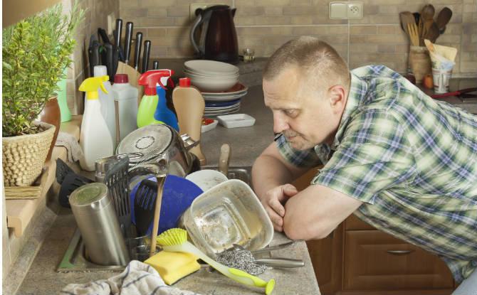 גברעומד ליד כיור מלא כלים