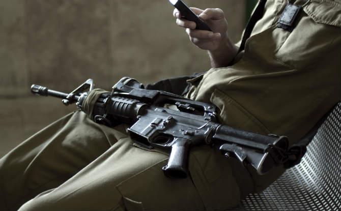 חייל יושב עם נשק עליו